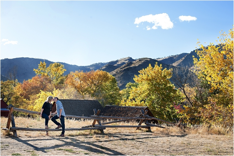 couple sitting on fence with trees and mountains, clear creek history park, golden colorado engagement session, autumn, l elizabeth events, colorado engagement photography, mountain engagement photographer