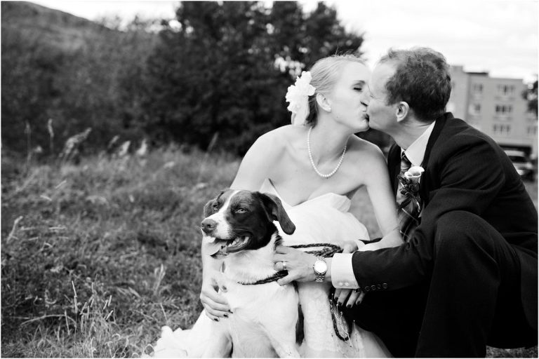 bride and groom kissing with dog in field at clear creek history park, black and white image, golden, colorado wedding photographer, mountain wedding planner