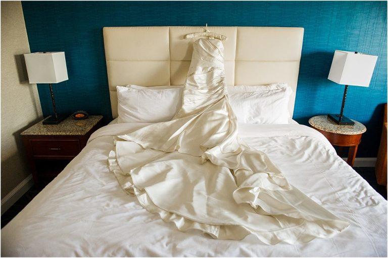 colorado wedding planner, wedding dress, detail photo, summer wedding, fourth of july, white dress on bed with blue wall, l ellizabeth events, wedding planning